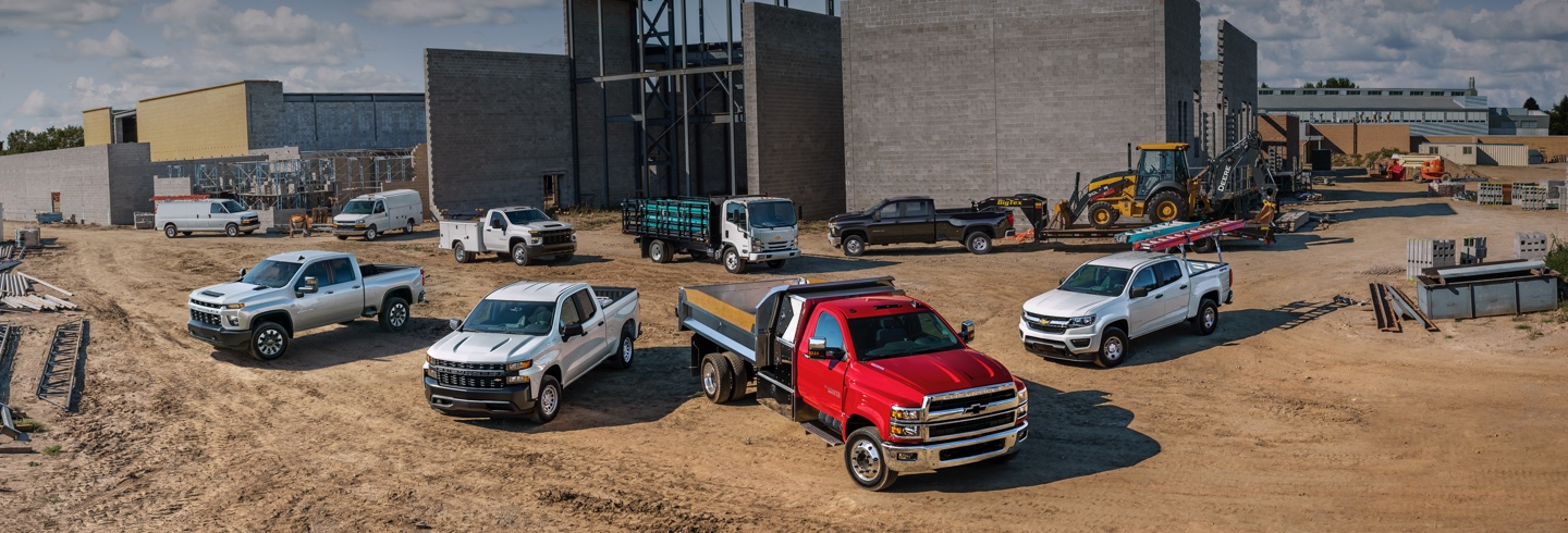 A couple of Chevrolet trucks parked in a construction field.